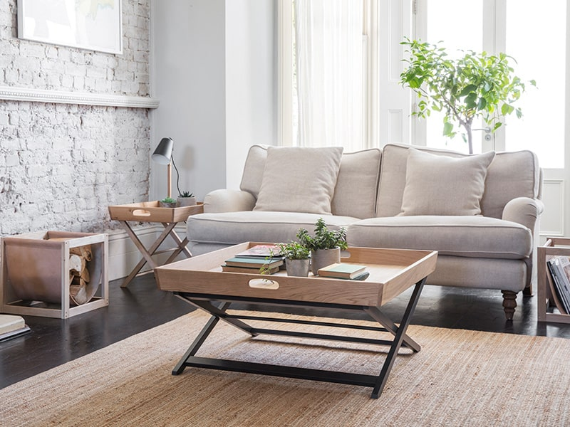 Neutral coloured living room with cream sofa, wooden coffe table, side table with lamp and oak and leather log basket