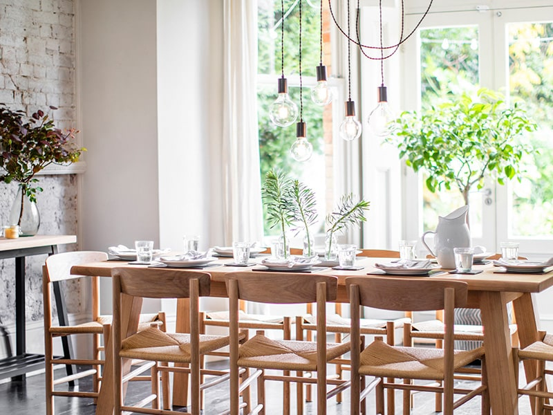 Pendant lights draped above a dining table laid with glasses, plates and vases