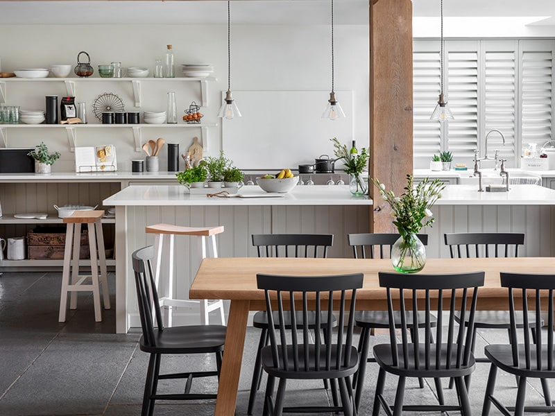 Open plan white kitchen with dining table, island with bar stools and lighting