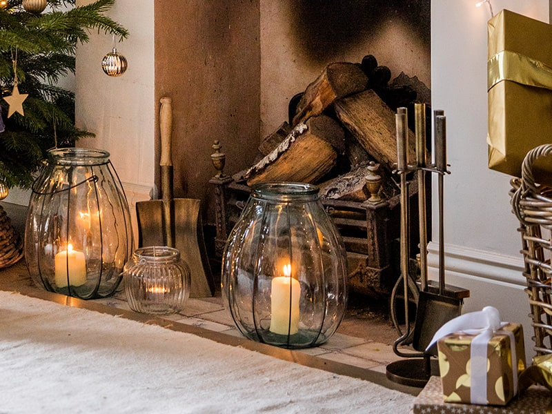 Cosy fireplace with large candles and brass fireside tool sets