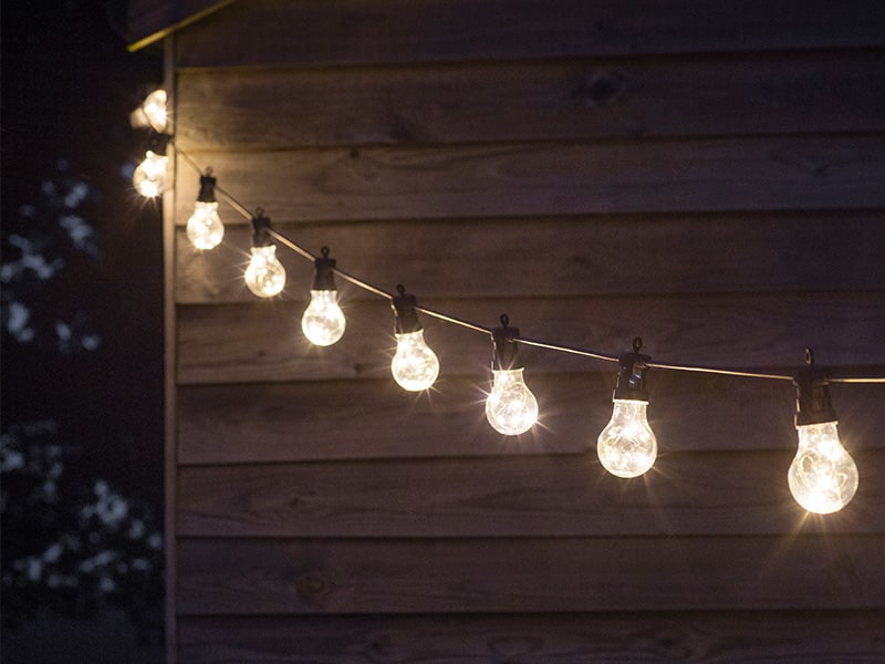 Glowing string of Festoon lights strung up along an outdoor building in the evening