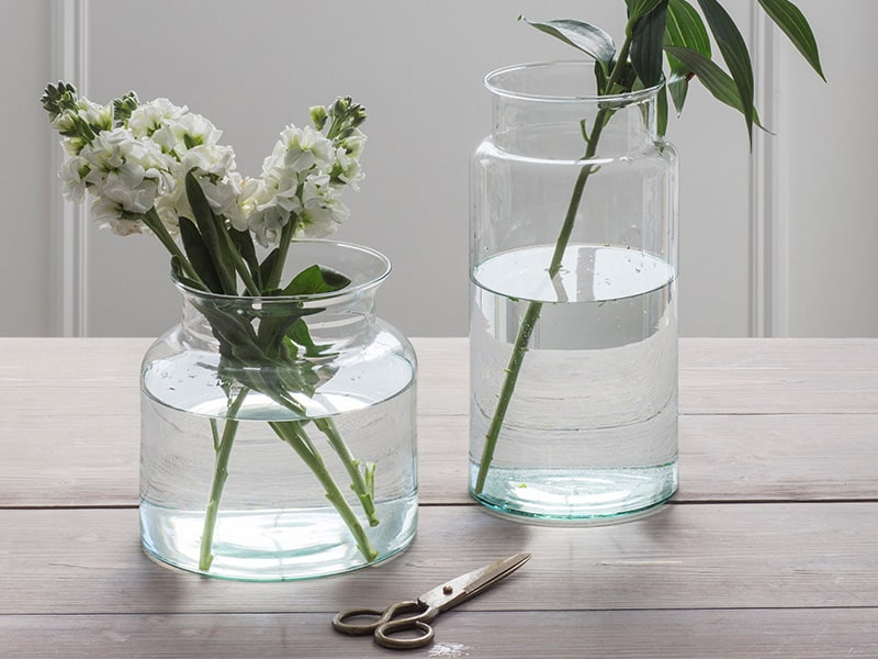 Cut flowers in clear recycled vases on a table
