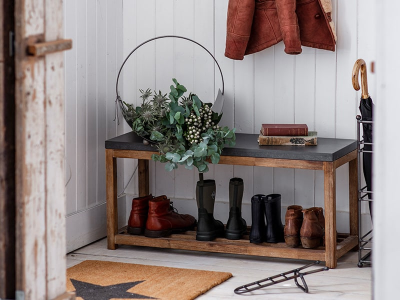 Entrance hallway with storage bench, large star doormat and winter foliage in a round steel carrier