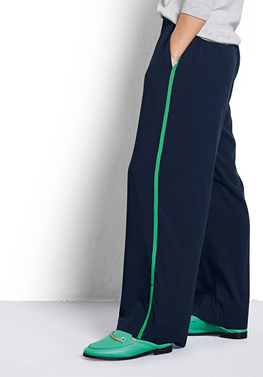Model wears our Wide leg trousers with contrast trim in midnight with a jolly green side stripes
