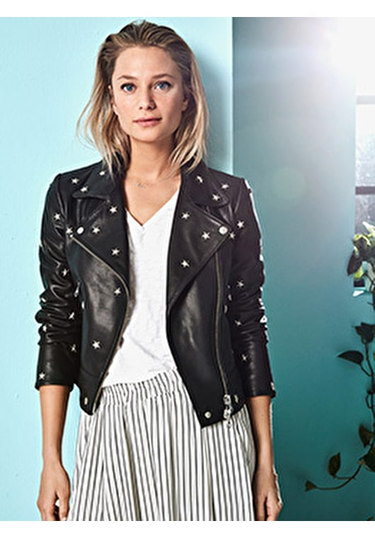 Model wears our black leather jacket with metal star shaped studs in a relaxed style