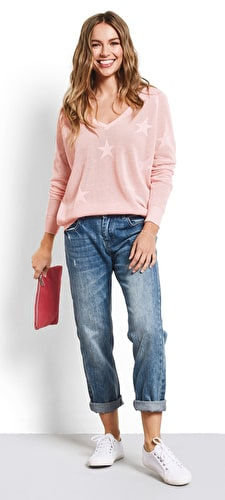 Model wears our V neck lightweight knitted jumper with delicate stars in a primrose pink