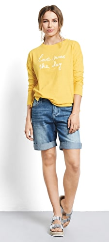 Women wearing our long denim shorts in a slouchy fit with turned up hems