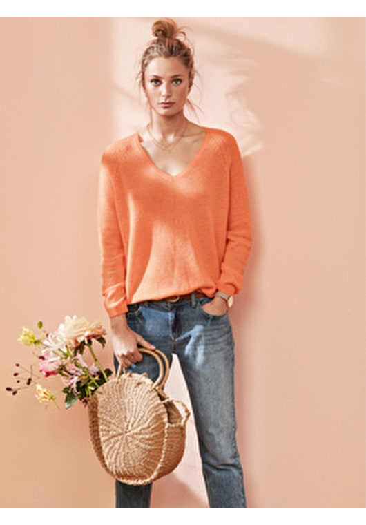 Woman wearing our super soft, semi sheer v neck cashmere jumper in a stunning Neon orange.