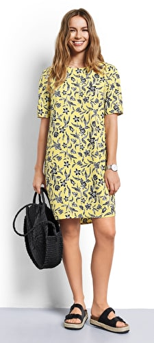 Model wears our floral print dress in a straight cut style with a scoop neckline short sleeves in a stunning yellow