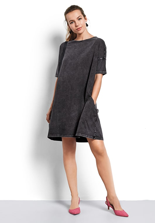 Model wears our oversized t shirt dress in a beautiful washed black with a scoop neck and short sleeves