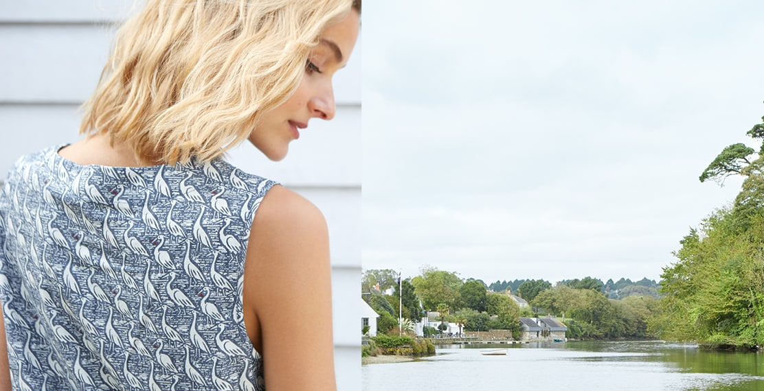 Blonde haired lady wearing a navy heron bird print sleeveless top & a scenic photo of the Hellford River.