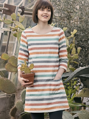 Dark haired lady wearing a Stripey Tunic in front of cacti