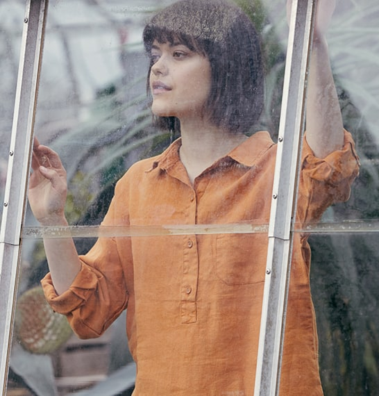 Dark haired lady looking outside the Potager greenhouse wearing a burnt orange tunic