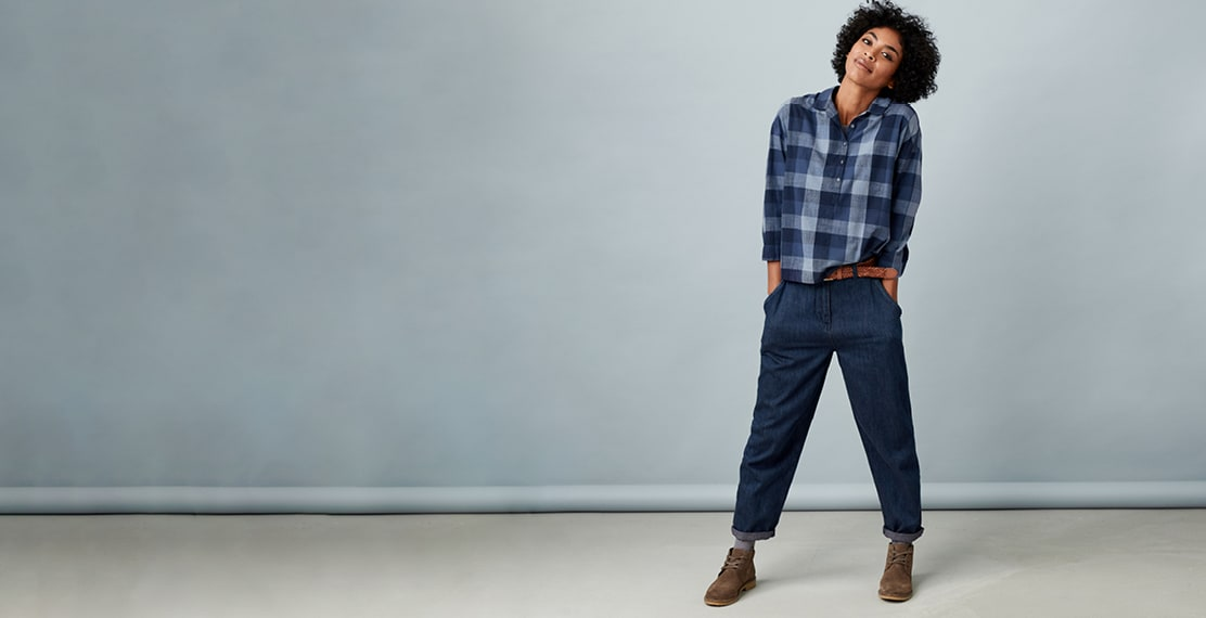 Lady wearing a checked shirt & turned up jeans posing with her hands in pockets