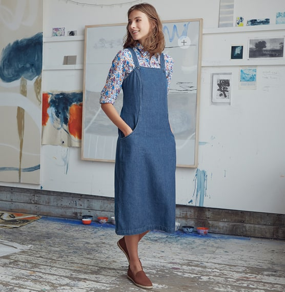 A women wearing a denim pinfore dress with abstract painting on the wall in the studio