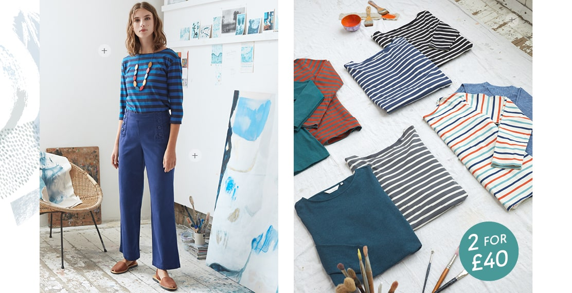 Women wearing a Stripey top & blue trousers in the Porthmeor studio with paintings on the walls next to her.